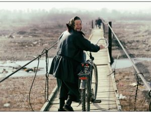 woman crosses a footbridge with bicycle