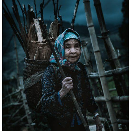 an old woman carries wood near mu cang chai