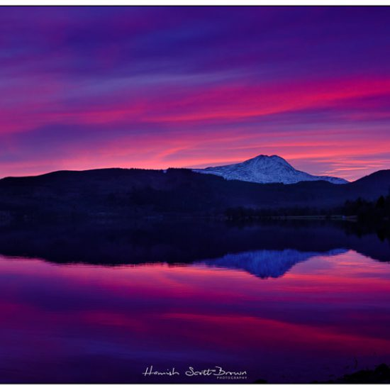 red sun sets with a red sky over ben lomond and loch Ard