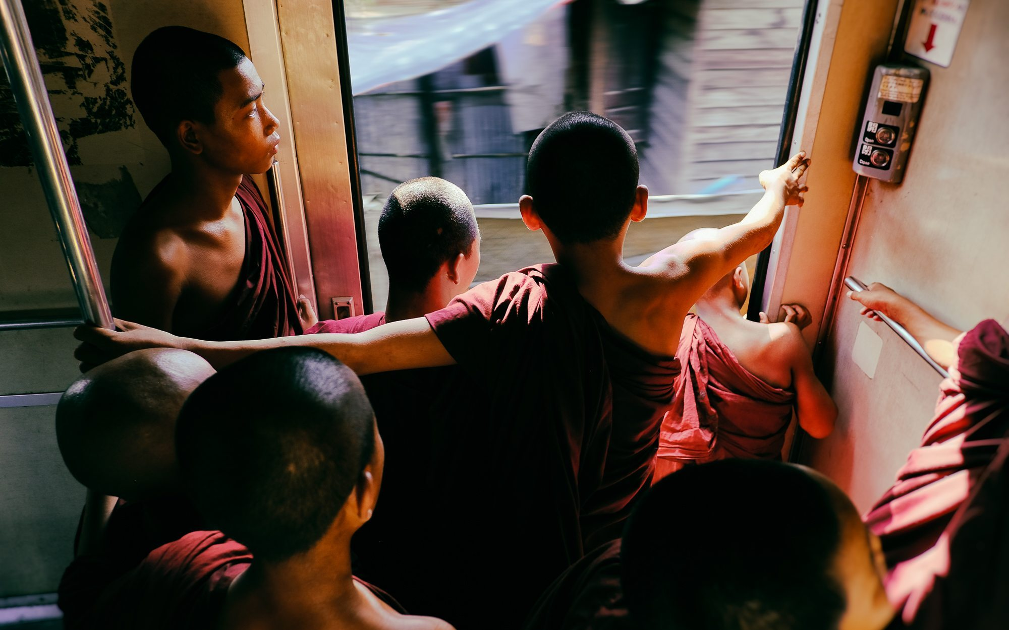 young buddhist monks on a moving train in central myanmar © Hamish Scott-Brown