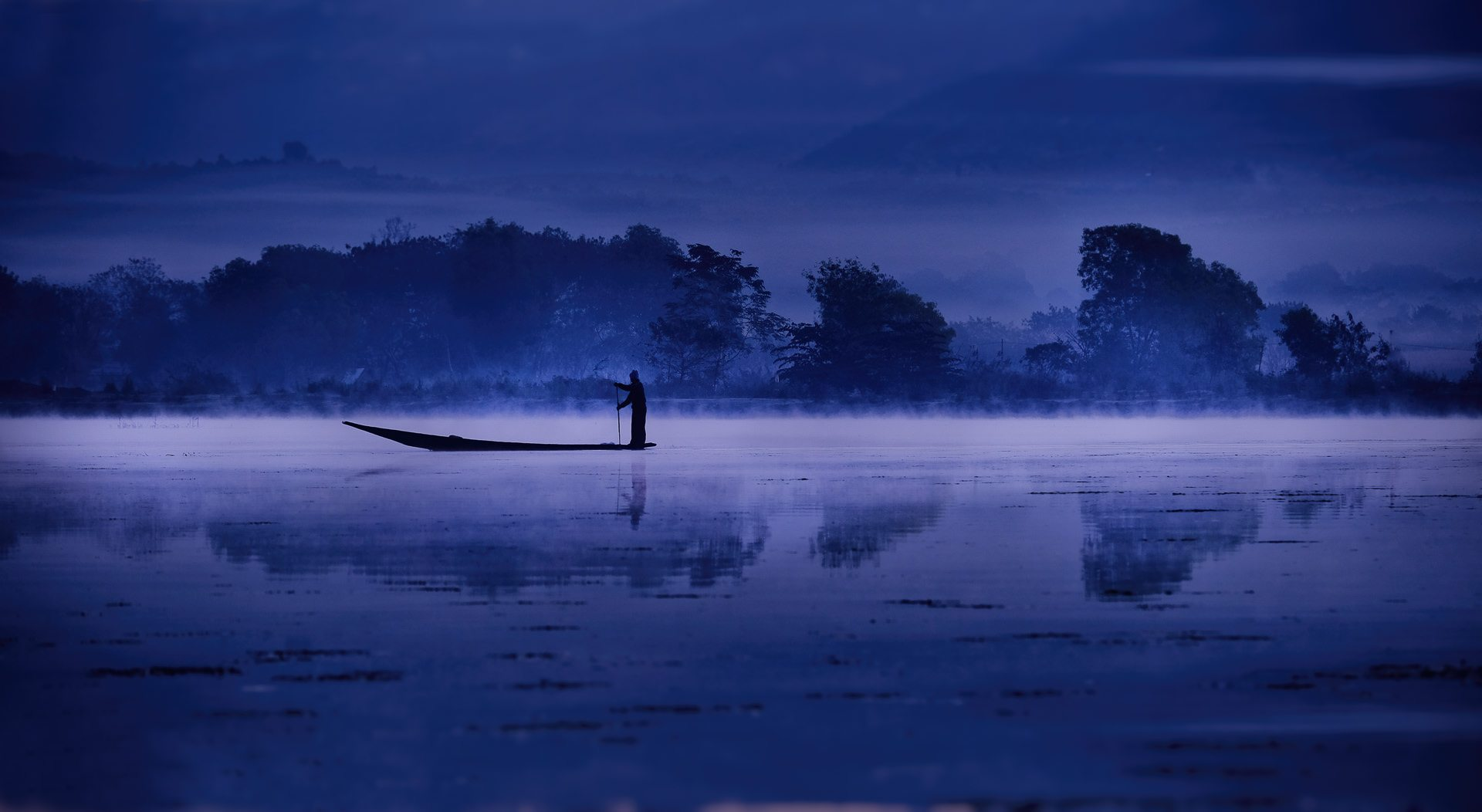 mist rises at dawn as a fisherman paddles across Inle lake, Myanmar © Hamish Scott-Brown