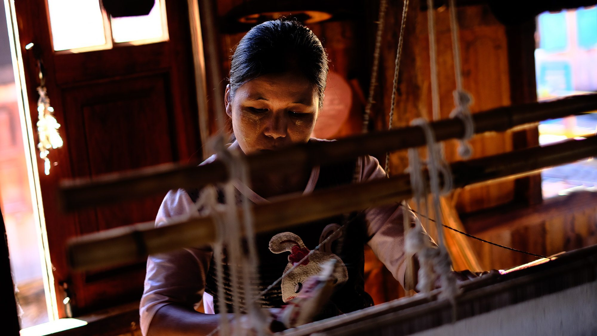 a burmese textile weaver on inle lake working at a loom © Hamish Scott-Brown