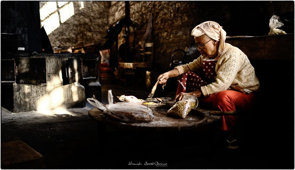 Burmese kitchen with a cook preparing vegetables © Hamish Scott-Brown