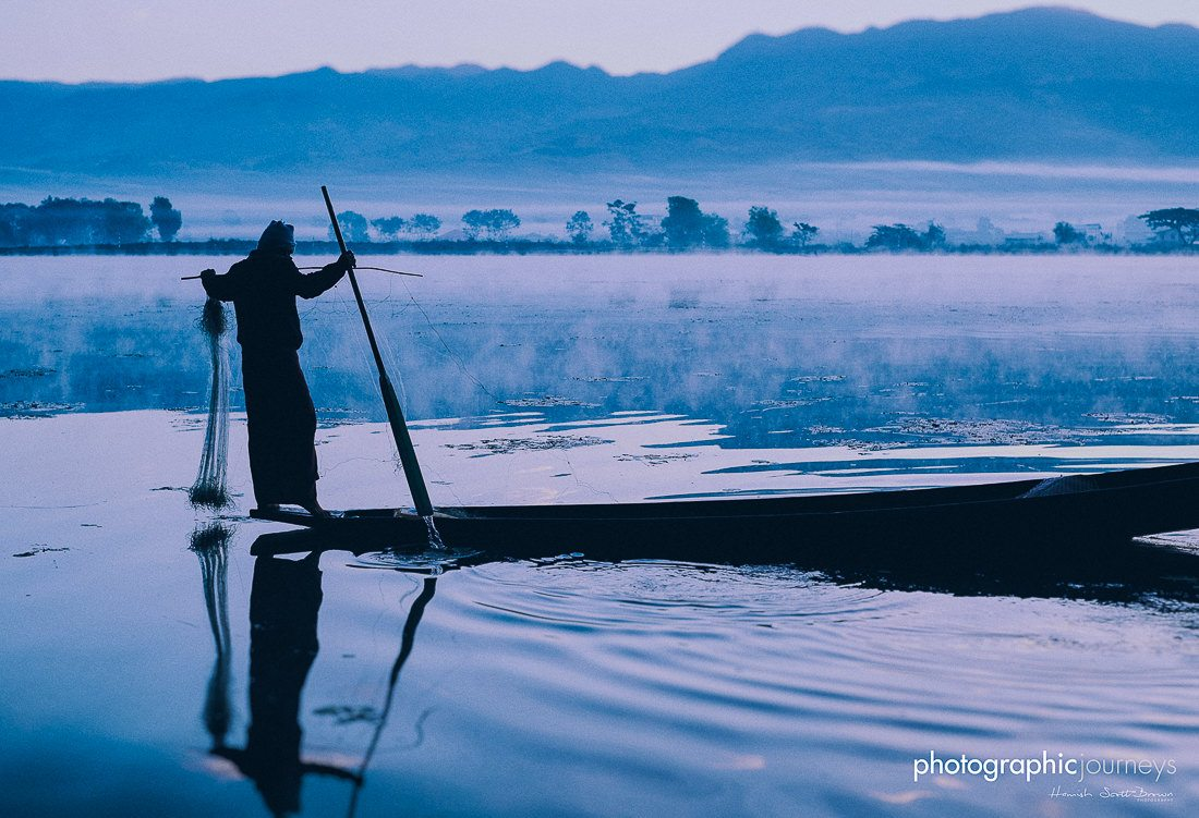 A fisherman tends his nets as dawn light rises over Inle Lake, Shan State , Myanmar © Hamish Scott-Brown