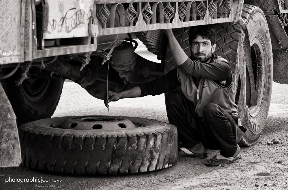 truck driver changes a wheel in india © Hamish Scott-Brown
