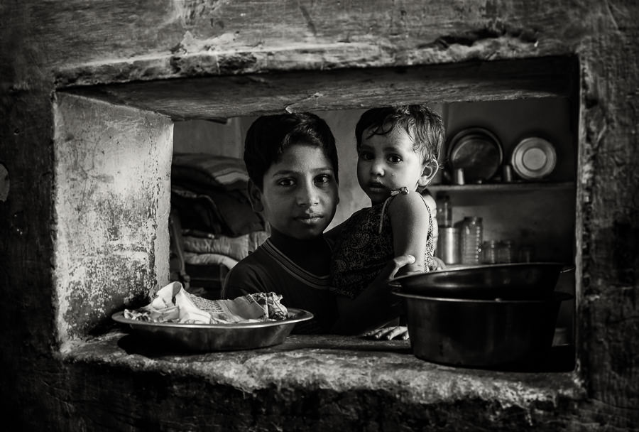 a small kitchen window with its owner in a slum outside of jaipur © Hamish Scott-Brown