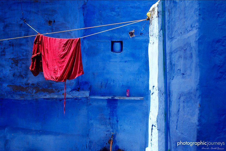 red washing hangs drying against a blue wall jodhpur © Hamish Scott-Brown